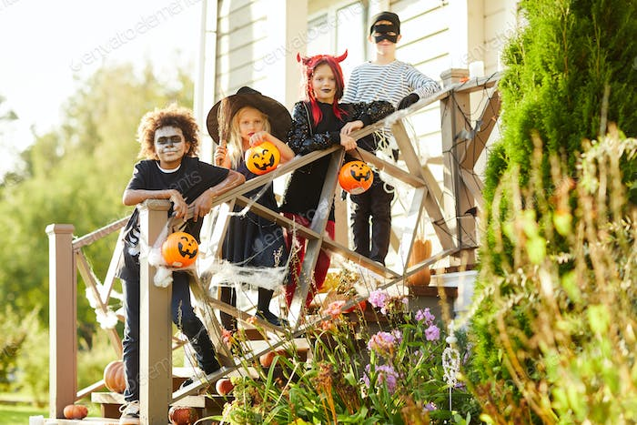 Friends Posing by Decorated House on Halloween
