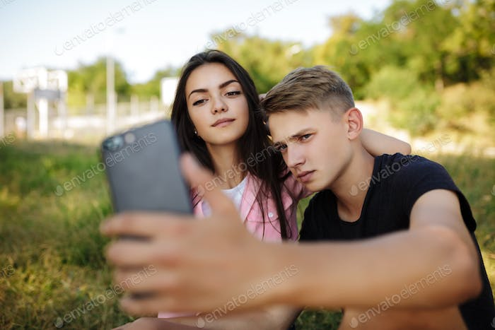 Young beautiful couple sitting on lawn in park and making selfie