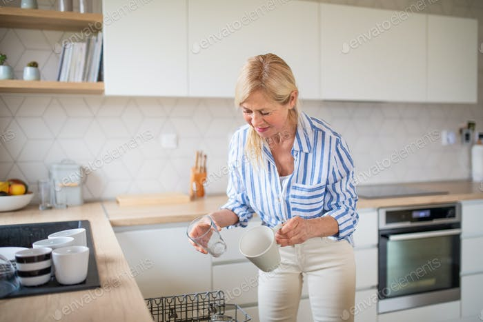 Senior woman loading or unloading dishwasher indoors at home