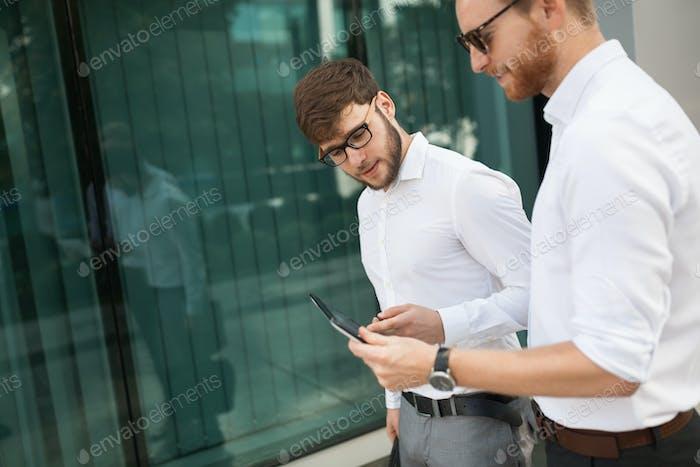 Geschäftsleute schauen auf Tablette