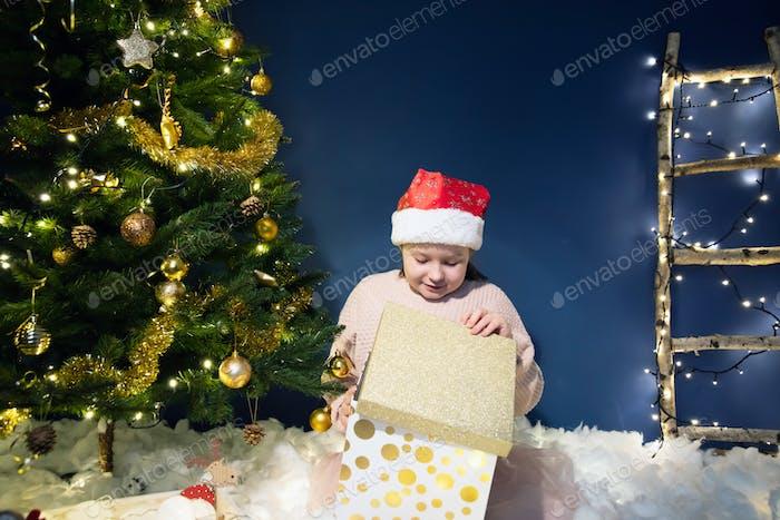 Christmas, holidays and childhood concept - cuti little girl having fun near the Christmas tree.