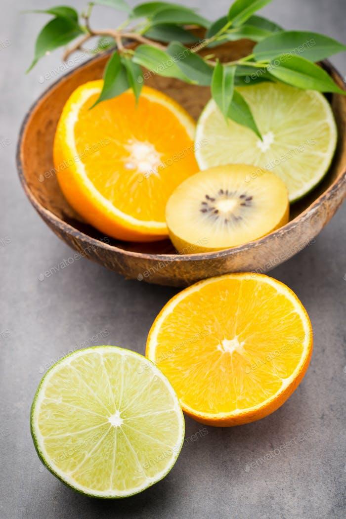 Mixed citrus fruit lemons, orange, kiwi, limes on a gray background.
