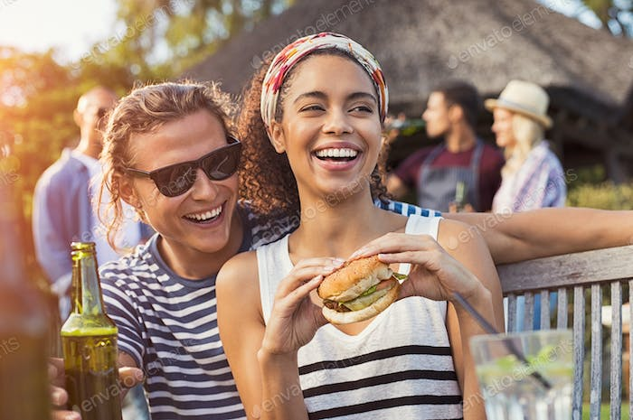 Couple enjoying food and drinks at party