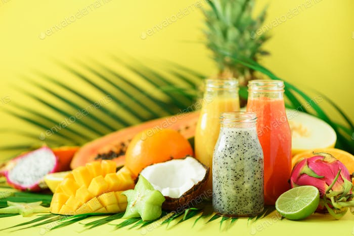 Juicy papaya and pineapple, mango, orange fruit smoothie in jars on yellow background. Detox, summer