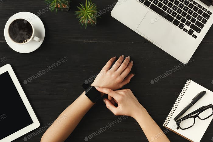 Woman's hands and smart watch, top view