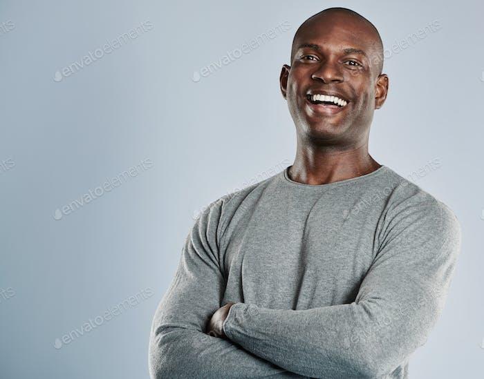 Lachender afrikanischer Mann in grauem Hemd mit Kopierraum