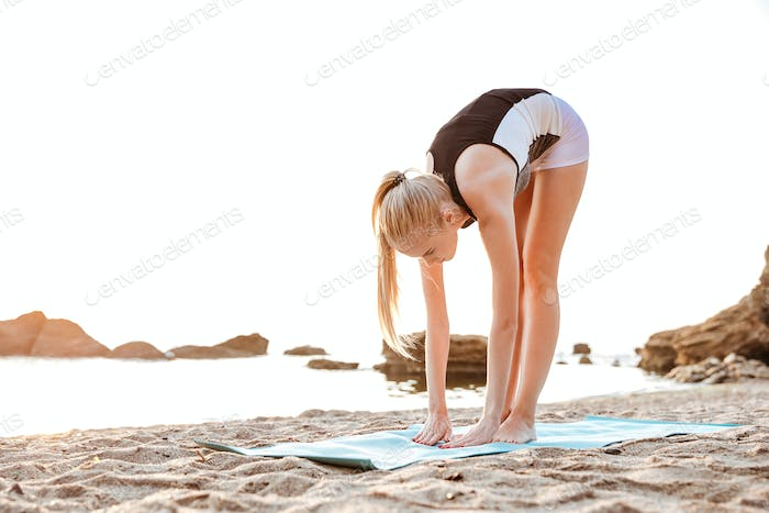Young woman doing yoga exercises on mat outdoors
