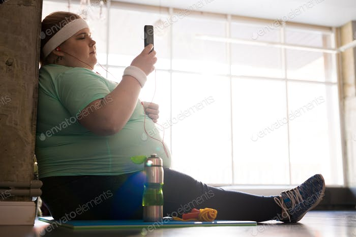 Obese Woman Using Smartphone after Workout