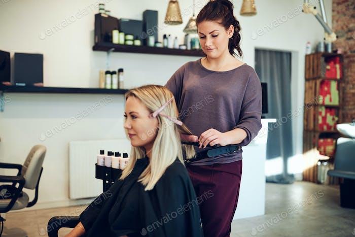 Hairdresser straightening a client's long blonde hair in her salon