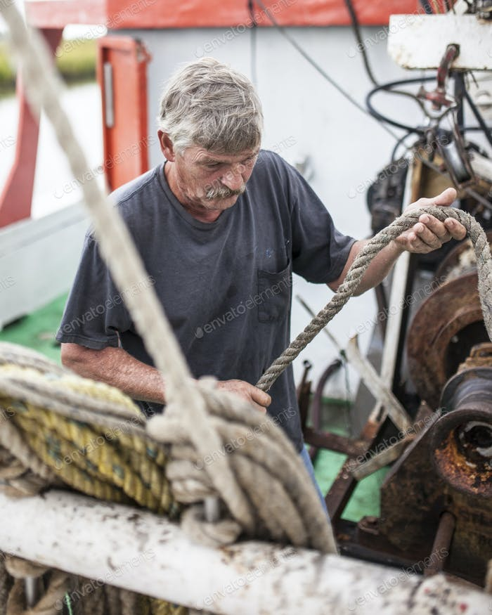 A commercial fisherman loads a rope onto a winch on a fishing boat.