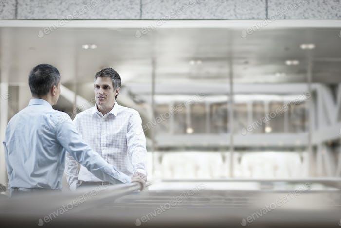 Zwei Männer, Geschäftskollegen, stehen im Gespräch.
