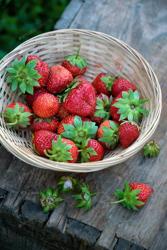 Ripe strawberries with leaves in a basket