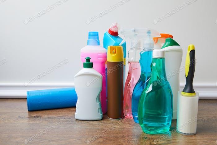 Flaschen mit Reinigern und Sprühflaschen auf dem Boden