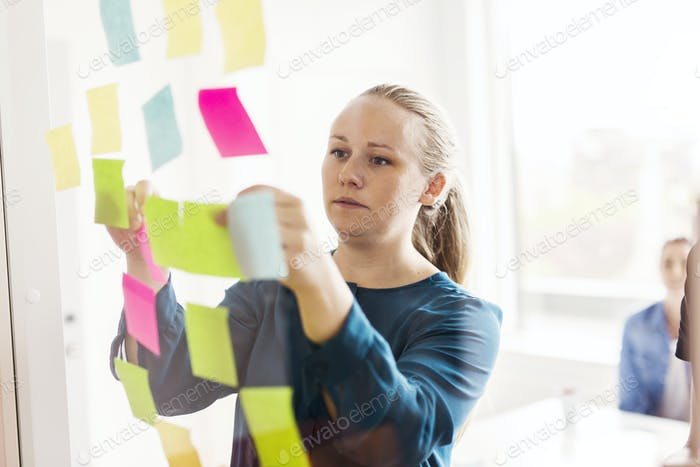 Young woman looking at adhesive notes