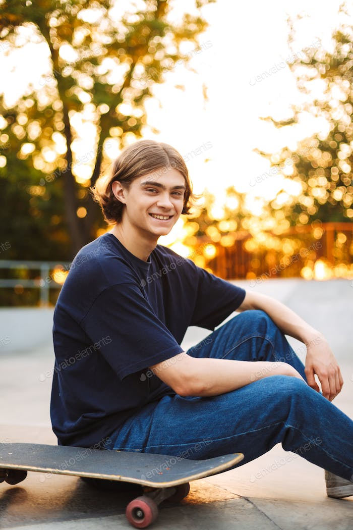 Young smiling skater in black T-shirt and jeans joyfully looking