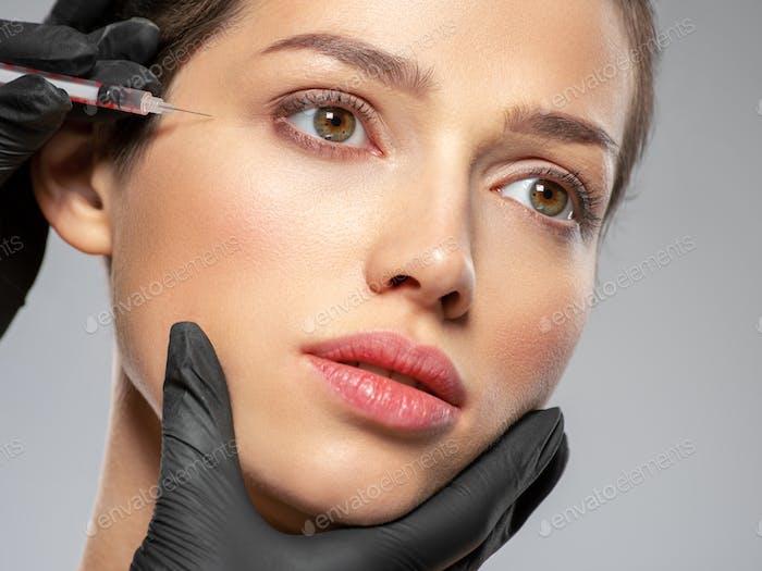 Kaukasische Frau bekommt Botox kosmetische Injektion in der Stirn. Frau bekommt botox Injektion in Ihr Gesicht