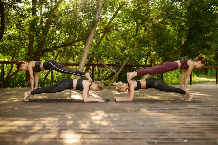 Four women doing balance exercise, group yoga