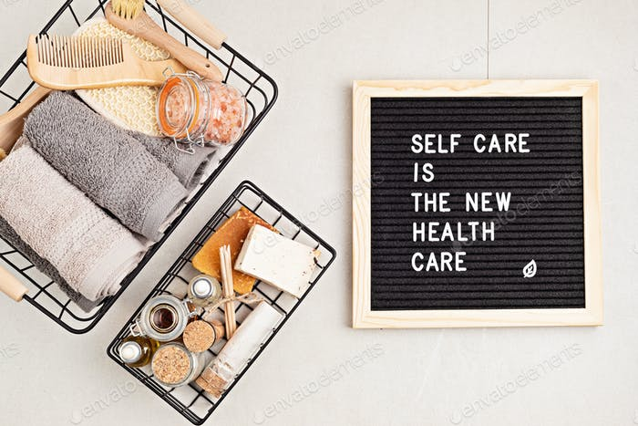 Self care is the new health care. Motivational quote on black letter board with variety of organic