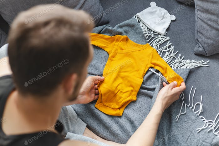 Young father preparing clothes for baby
