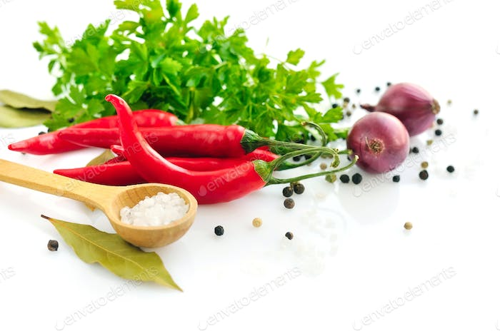 Parsley, garlic clove, onion, red pepper and spices on white bac