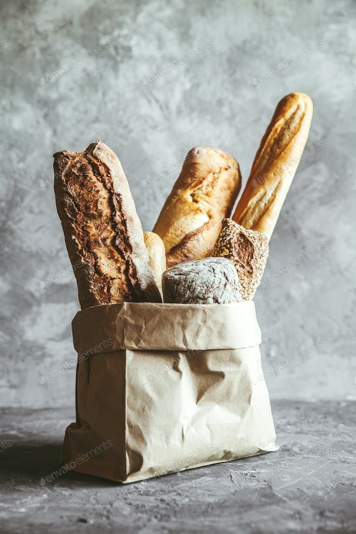 French pastries, baguettes on a gray background in a paper bag
