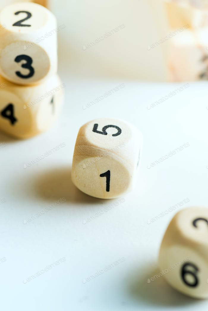Wooden cubes with numbers on a light grey background. Dice game concept