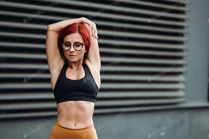 Fitness concept - attractive fit woman stretching arms