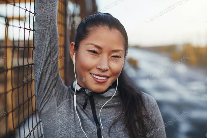 Smiling Asian woman in sportswear listening to music before jogging