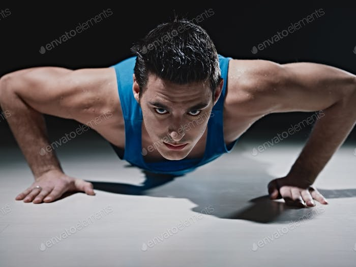 Man Doing Push-ups On Black BackgroundMan Doing Push-ups On Black Background
