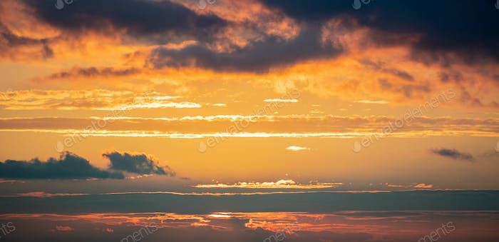 Sunrise clouds. Dramatic magical sunset over orange cloudy sky