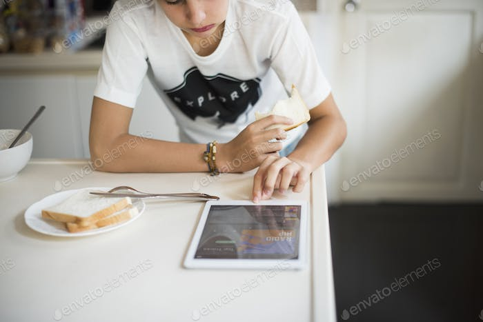 Young caucasian man using digital tablet in the kitchen