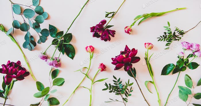 Flat-lay of various summer flowers over pink background
