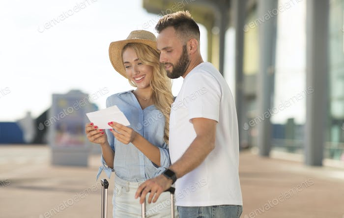 Happy couple looking at boarding pass checking departure time