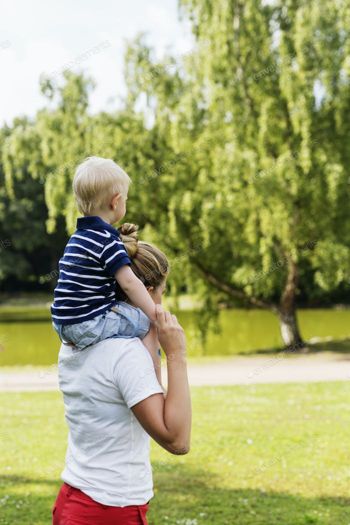 Side view of woman carrying son on shoulders in park