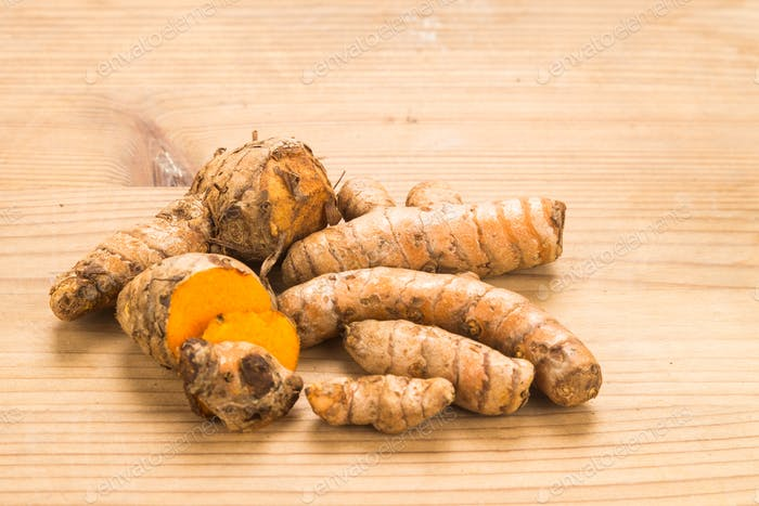 Fresh turmeric roots with wellness properties on wooden surface.