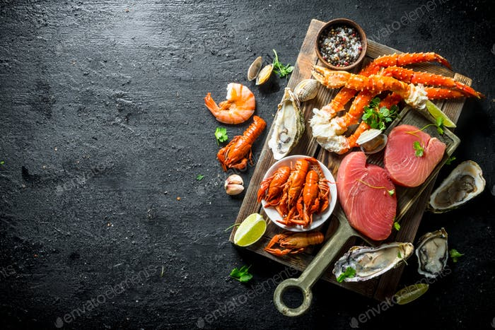 Raw tuna steak and seafood on wooden tray.
