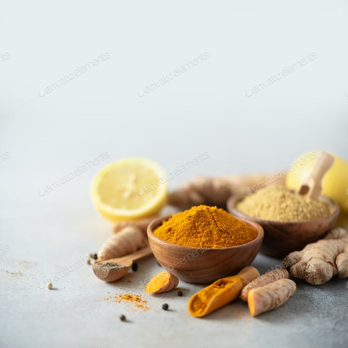 Ingredients for turmeric latte. Turmeric powder, curcuma root, cinnamon, ginger over grey background