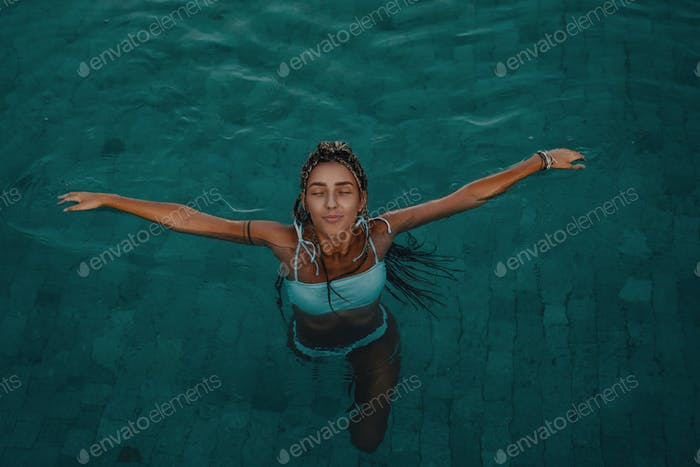 Tanned woman in swimsuit swimming in pool
