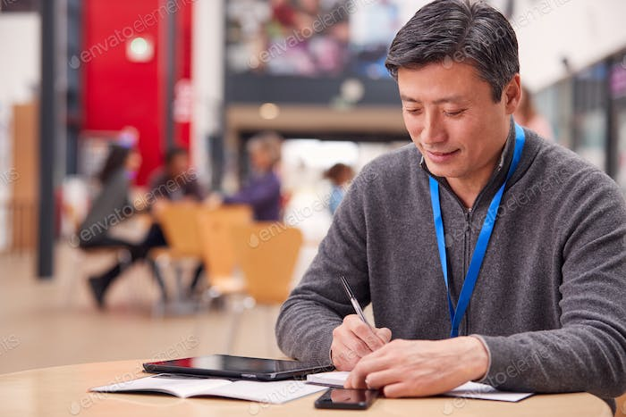 Mature Male Teacher Or Student With Digital Tablet Working At Table In College Hall