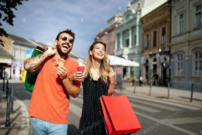 Beautiful young loving couple walking by the street while shopping and traveling