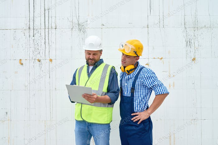 Bauarbeiter diskutieren Gebäude