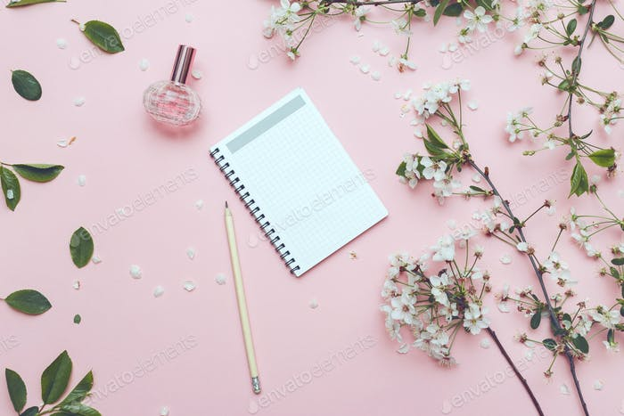 Notebook with pencil, perfume jar and blossom fower on blue rustic table from above