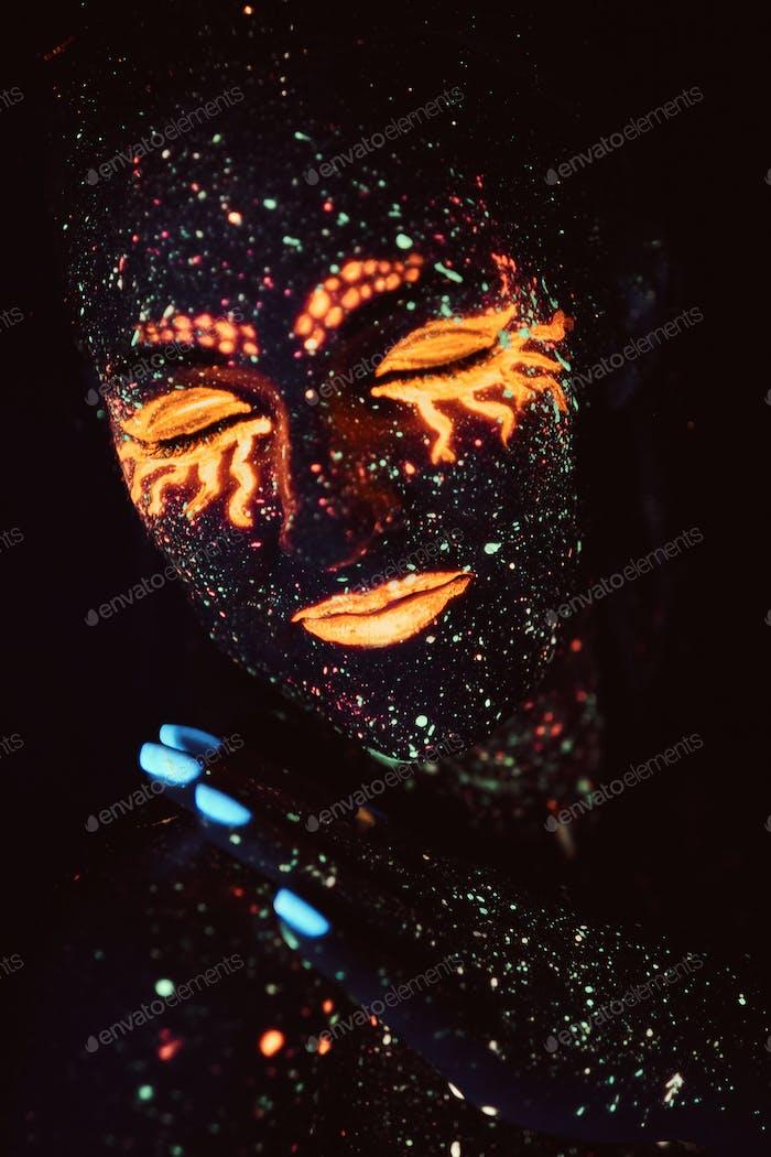Porträt eines Mädchens in fluoreszierendem Pulver gemalt. Halloween-Konzept.