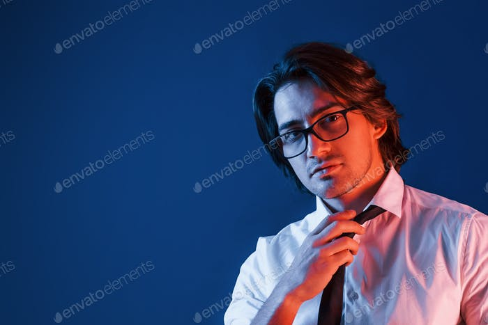 Beautiful man in formal wear and in glasses is in the studio with blue neon lighting