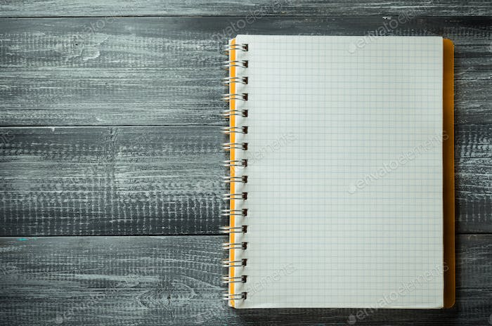 checked notebook on wooden table