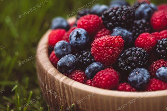 raspberries and blackberries in wood bowl on table, vintage