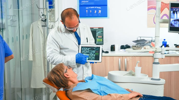 Orthodontist in gloves holding tablet suggesting treatment
