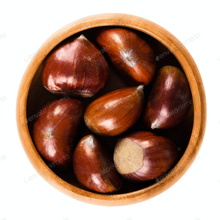 Sweet chestnuts in wooden bowl on white background