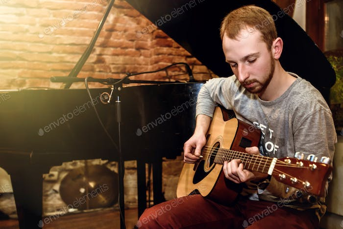 stylish solo guitarist performing on a concert on a background of his band