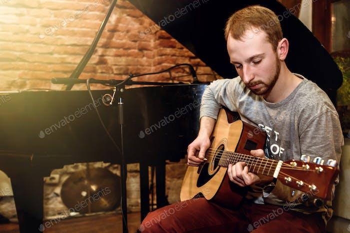 stilvoller Solo-Gitarrist auf einem Konzert auf dem Hintergrund seiner Band